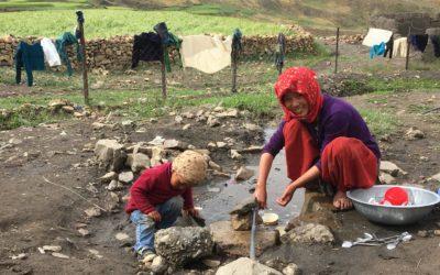 Frau mit Kind spült ihr Geschirr an einem Rinnsal im Dort Demul (Spiti)