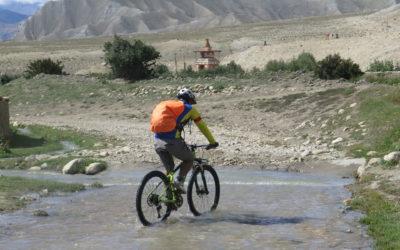 Nepal: Mountainbiker durchquert ein kleines Flüsschen.