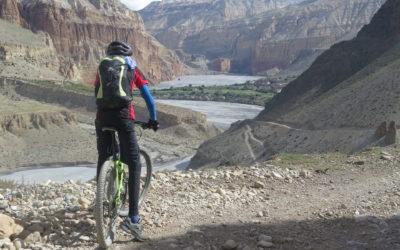 Nepal, Mustang per Mountainbike. Mountainbiker genießt den Blick auf die Felsformationen im Kali-Gandaki-Tal.